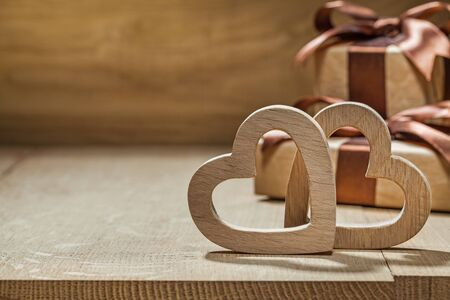 wood hearts and gift boxes close up wooden background Imagens