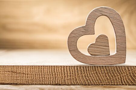 vintage wood hearts on wooden background close up view