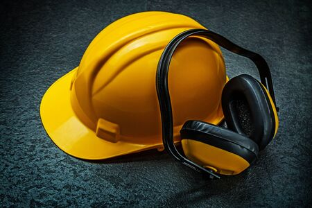 yellow helmet and earphones on blackbackground Stock Photo