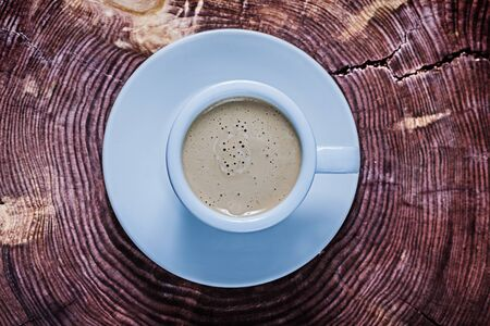 view from above capuchino in white ceramic cup on vintage cross section tree trunk