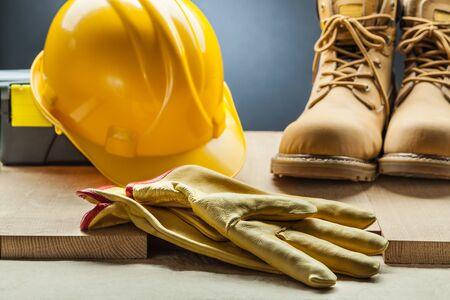 gelbe Lederhandschuhe Arbeitsstiefel Bauhelm Werkzeugkasten