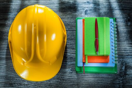 Set of notebooks pen safety hard hat on wooden board. Stockfoto