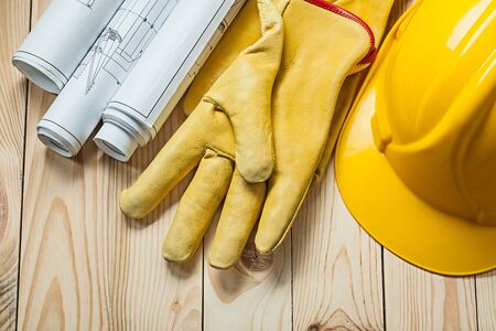 blueprints yellow gloves and construction helmet on wood boards 写真素材