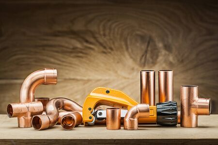copper pipe fittings and cutter on vintage wood background Archivio Fotografico - 127848895