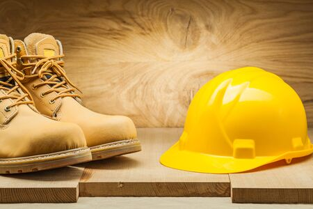 helmet with working boots on wood background