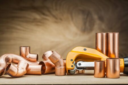 set of copper pipe fittings and  pipe cutter on vintage wood background Archivio Fotografico - 127848935