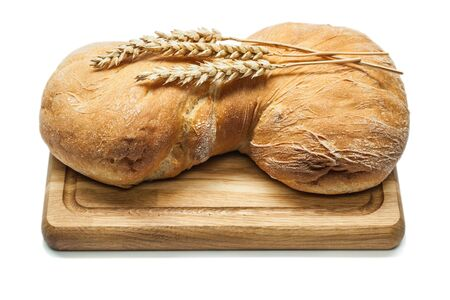 sweet bread on carving board and wheat ears isolated white