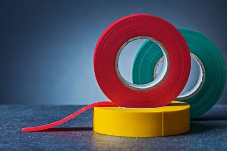 multy colored rolls of insulation tape on gradient gray background