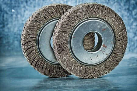 two abrasive flap discs on metalic background