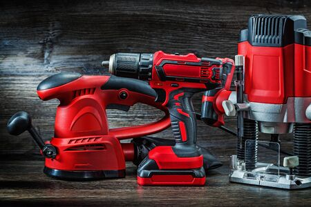 electric hand tools red wood sanding mashine corded jigsaw cordless drill and small plunge router milling machine portable mini wood router on vintage wooden background