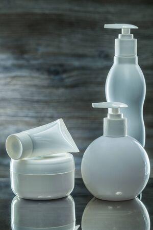 skincare items white sprayers and tube on dark background 写真素材