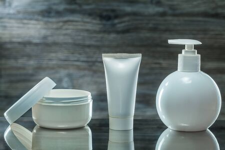 skincare items jar tube and sprayer on dark background 写真素材