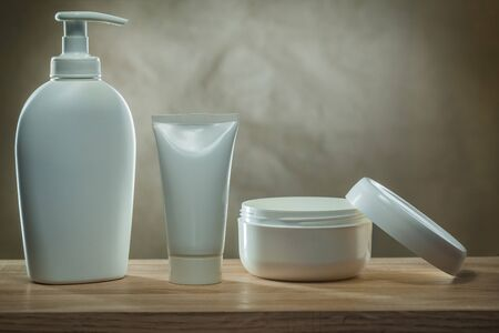 body hygiene products two pump dispensers mockup blank white plastic bottles and facial cream in opened jar on wooden table