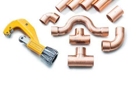 copper pipe and fittings with pipecutter isolated on white