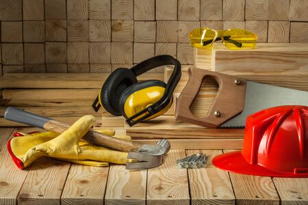carpentry tools goves helmet goggles hammer handsaw earphones nails handsaw on wooden background