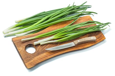 stems of spring green onion on wooden cutting board and kitchen knife isolated