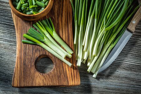 green chopped onions on wooden cutting board  kitchen knife vintage wood background Stok Fotoğraf