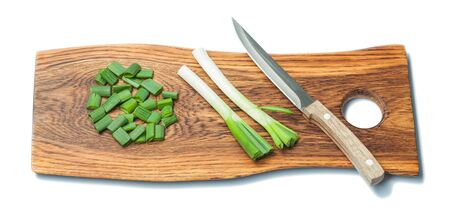 kitchen knife and chopped spring green onion stems on wooden chopping board isolated