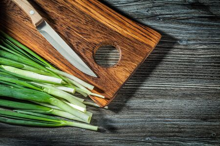 fresh spring green onions stems kitchen knife wooden chopping board on vintage wood background