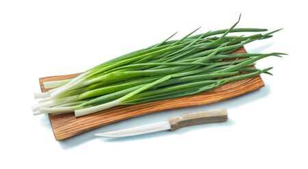 fresh green onion stems on wooden chopping board and kitchen knife isolated