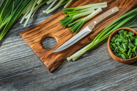 chopped green spring scallions kitchen knife wooden cutting board vintage wood background Stok Fotoğraf