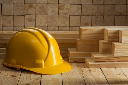 construction yellow helmet on wooden background