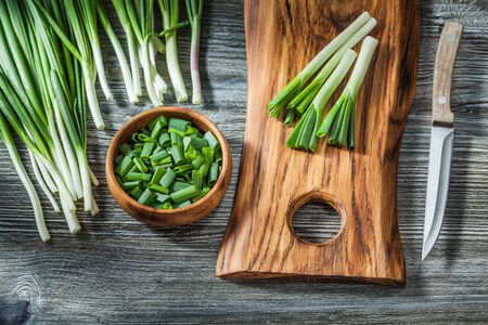 fresh green spring scallions wooden cutting board kitchen knife vintage wood background
