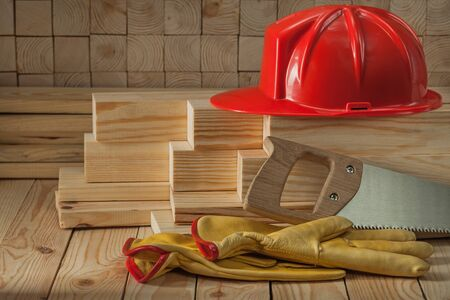 construction carpentry tools red helmet glaves and handsaw on wooden background Stok Fotoğraf