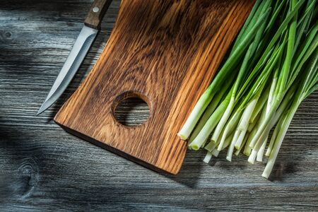 kitchen knife wooden chopping board fresh spring green onion stems on vintage wood background