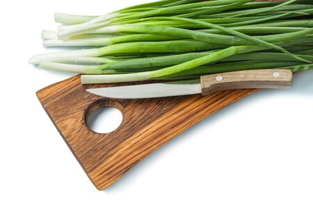 green scallions stems and kitchen knife on wooden chopping board isolated