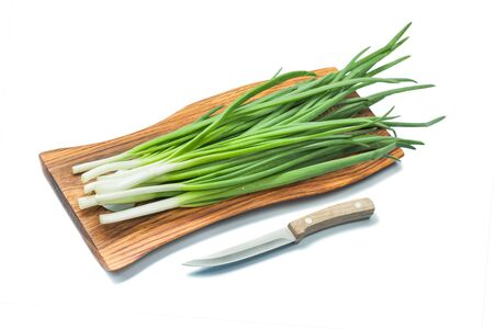 green scallion stems on wooden cutting board with kitchen knife isolated