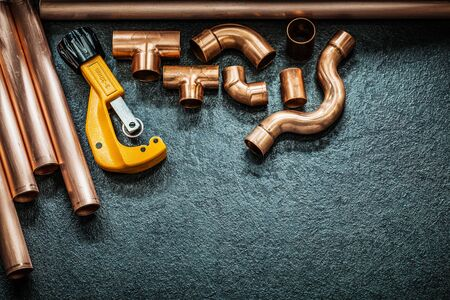 plumbing concept copper pipes pipe cutter and fittings on black background Archivio Fotografico