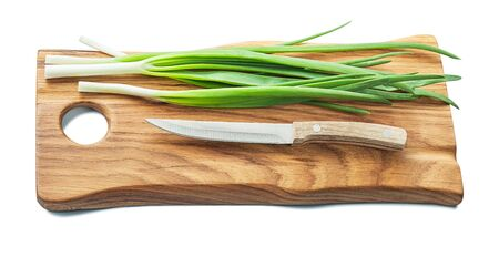 green onions and kitchen knife on wooden chopping board with life eddge isolated on white