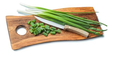 green chopped scallions and kitchen knife on vintage wooden chopping board with life eddge isolated