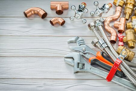 copper and brass plumbing fittings for connection pipes and adjustable wrenches on vintage wooden boards