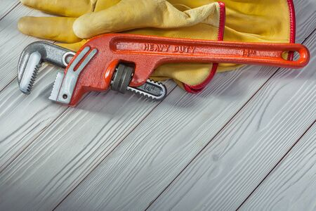 construction tools red plumbers monkey wrench and yellow work gloves on white vintage wood