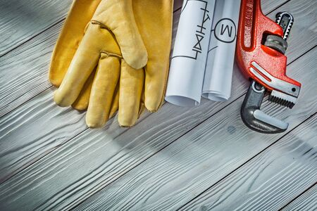 plumbing engineering rolled piping blueprints pipe wrench yellow leather work gloves on vintage white wood background