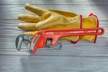 plumbers monkey wrench and yellow leather work gloves on vintage white painted wooden boards Фото со стока