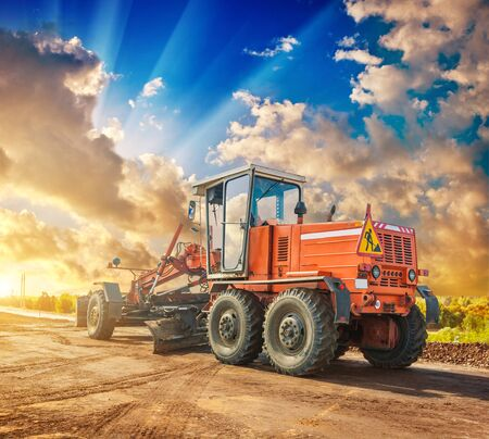 vintage construction tractor on wheels standing eddge of road beautiful sunset view