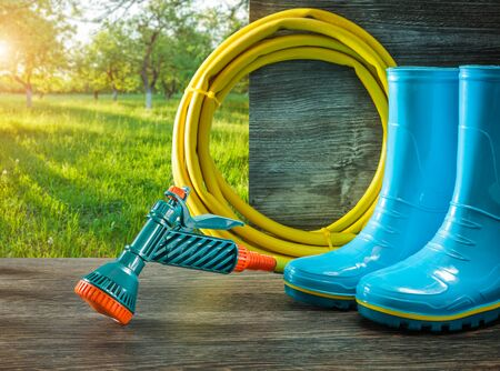 gardening tools watering hose with spray gan rain rubber boots on terrace in spring sunny garden