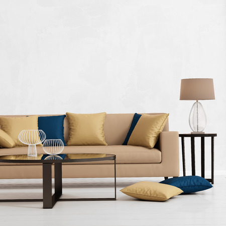 side table: Modern interior with a beige sofa, cushions and a side table Stock Photo