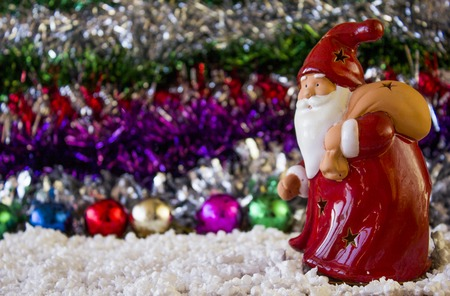 clause: Red Toy Santa Clause close-up on the tinsel, as babackground