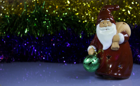 clause: red toy santa clause with reflection on the tinsel, as babackground