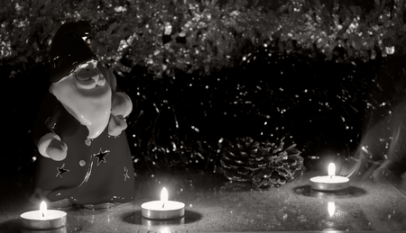 blak and white: night red santa clause with candles on the tinsel, as babackground