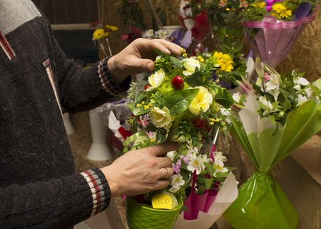 creates: Man creates a bouquet with ping ribbon