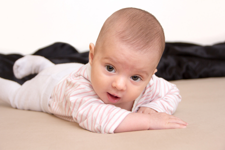 Neck Muscles getting stronger: Three months old baby girl lying on tummy and holding head
