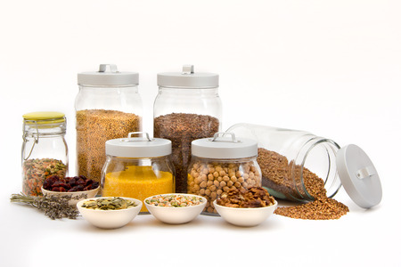 Glass Jars and cups with different sort of seeds and nuts isolated on white
