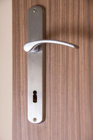 doorhandle: Door-handle on a brown wooden indoor door