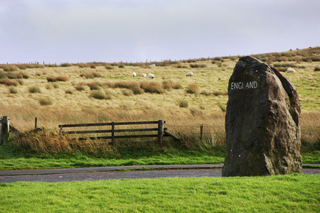 cumbria: England landscape with rock sign, fence and sheeps Stock Photo