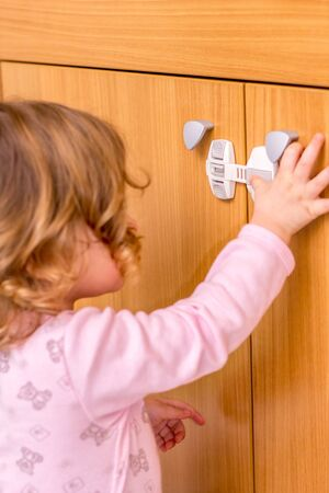 Baby girl trying to open the kitchen cabinet – baby proofing the door Stock Photo
